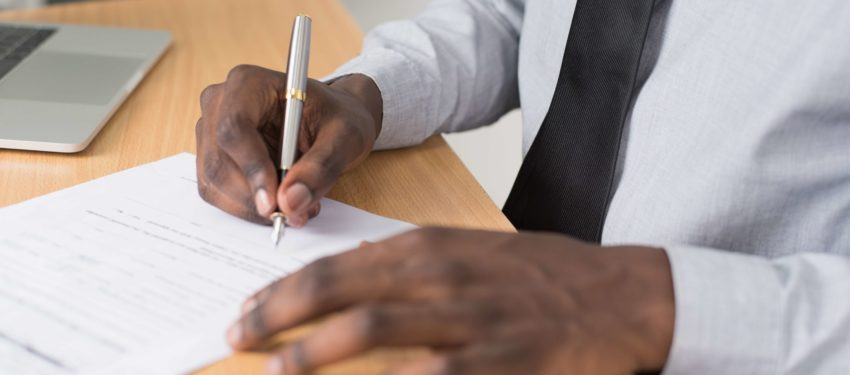 man holding a pen about to sign a piece of paper at his desk